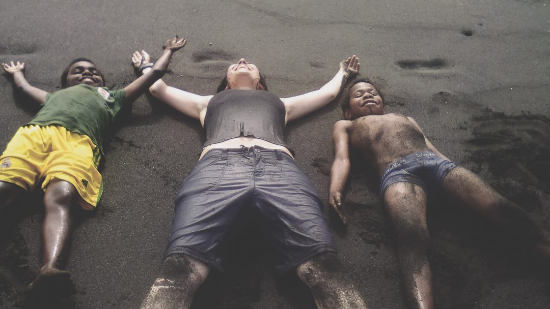 Researcher lying on the beach with children from Vanuatu